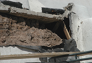 A slumped adobe wall under a concrete slab roof and behind Portland plaster at Isleta Pueblo Church, 2010.
